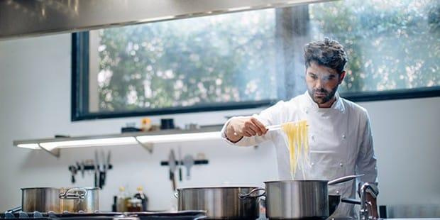 MAN cocina pasta en la cocina