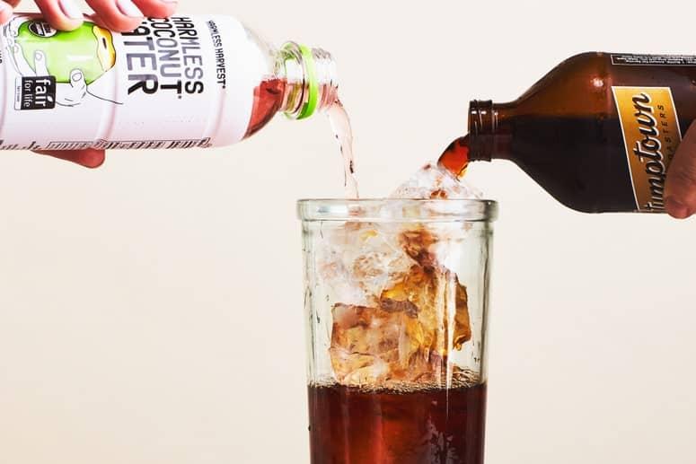 EL AGUA DE COCO Y LA CERVEZA FRÍA SE vierten en un vaso sobre hielo.