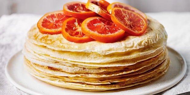 Pastel de crpe con rodajas de naranja en un plato