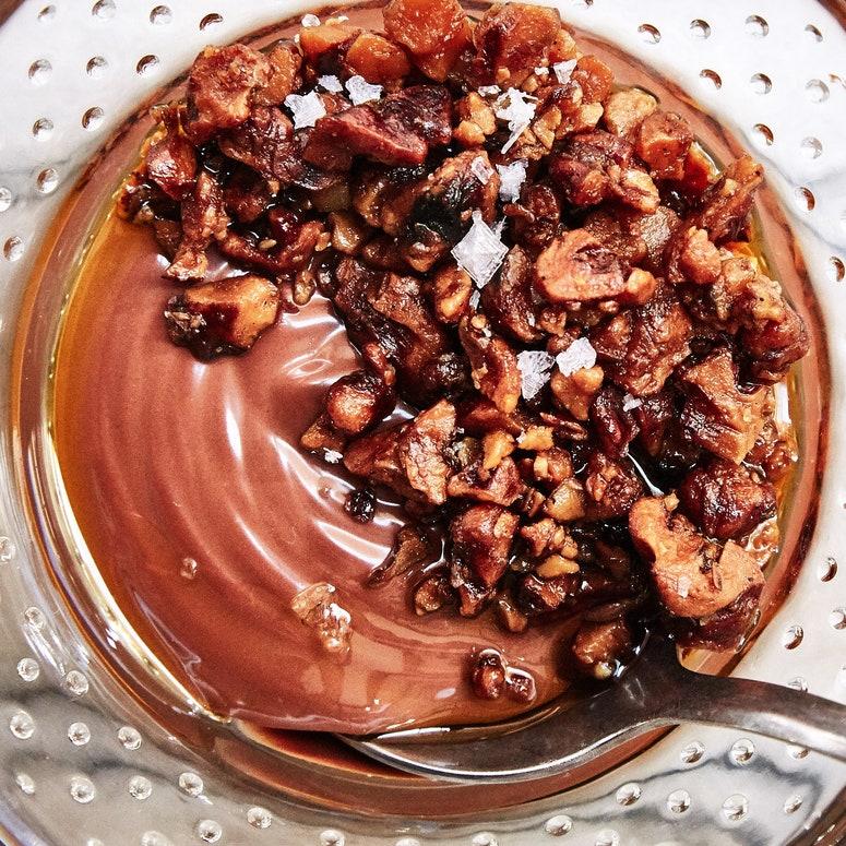 Recipiente de vidrio relleno de pudín de chocolate confitado y nueces con escamas de sal marina.