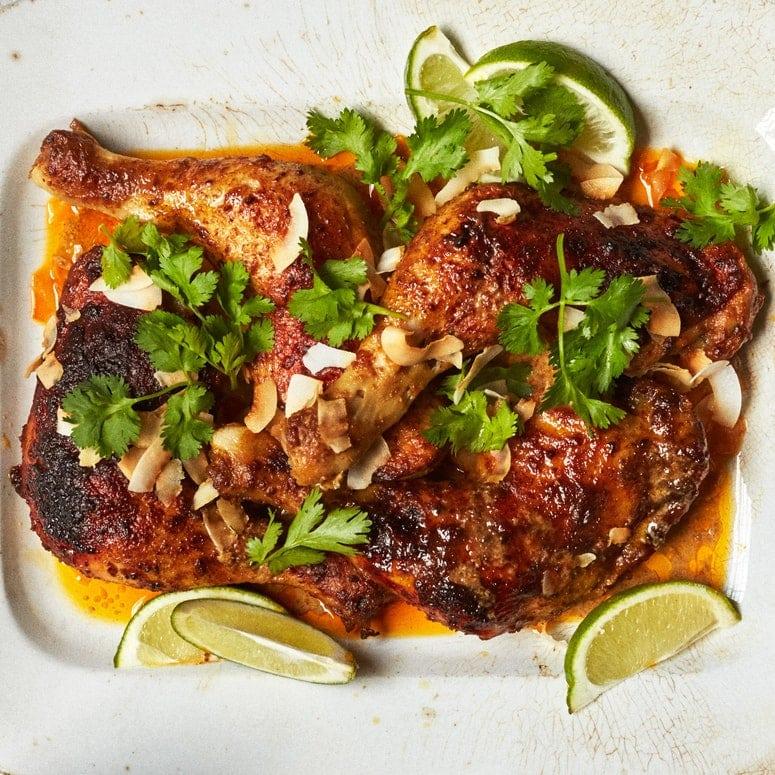 Piernas de pollo doradas apiladas en un plato y adornadas con hojuelas de coco tostado, rodajas de limón y cilantro.