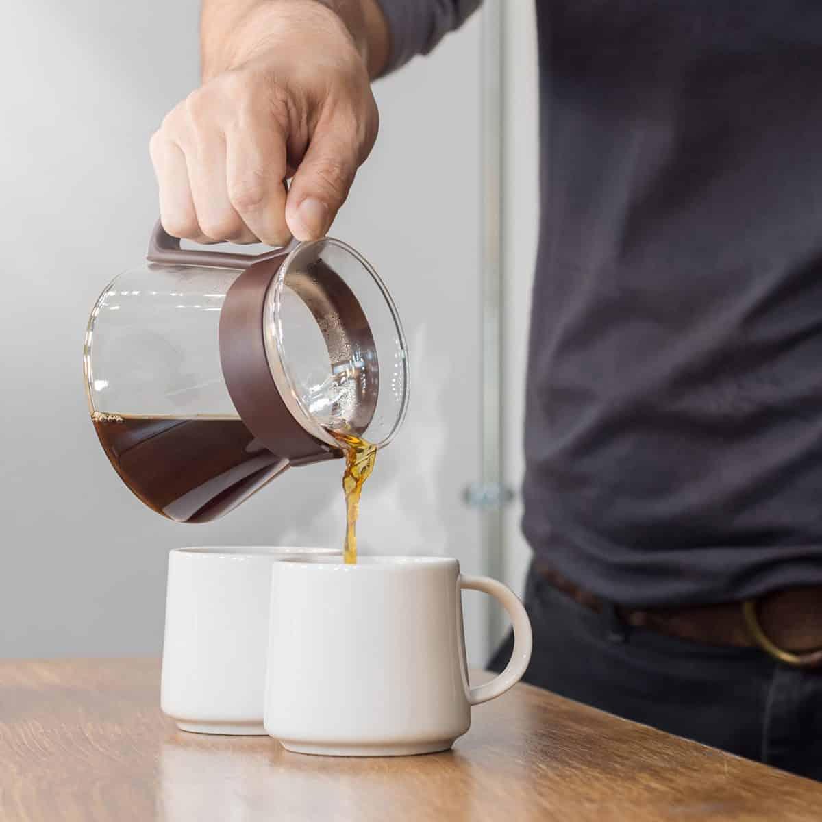 EL HOMBRE ESTÁ VERTIENDO CAFÉ CALIENTE DE LA CAFETERA EN EL CAFÉ CON LECHE EN LA MESA DE MADERA POR LA MAÑANA