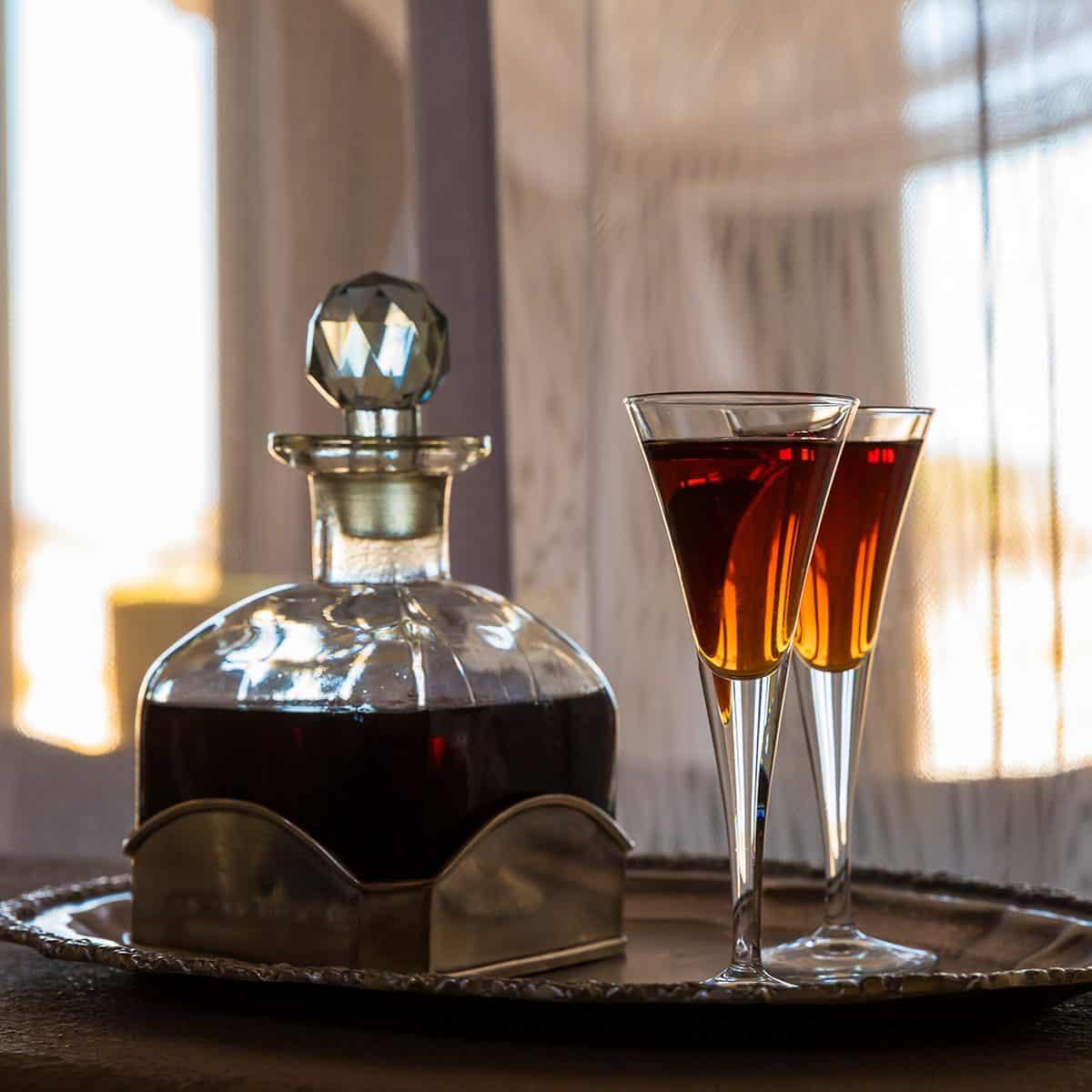 TWO GLASSES AN A CARAFE FILLED WITH RED SHERRY IN A ROOM SHUTTERSTOCK 1196871460 12 BEBIDAS PARA DESPUÉS DE LA CENA QUE DEBES SABER