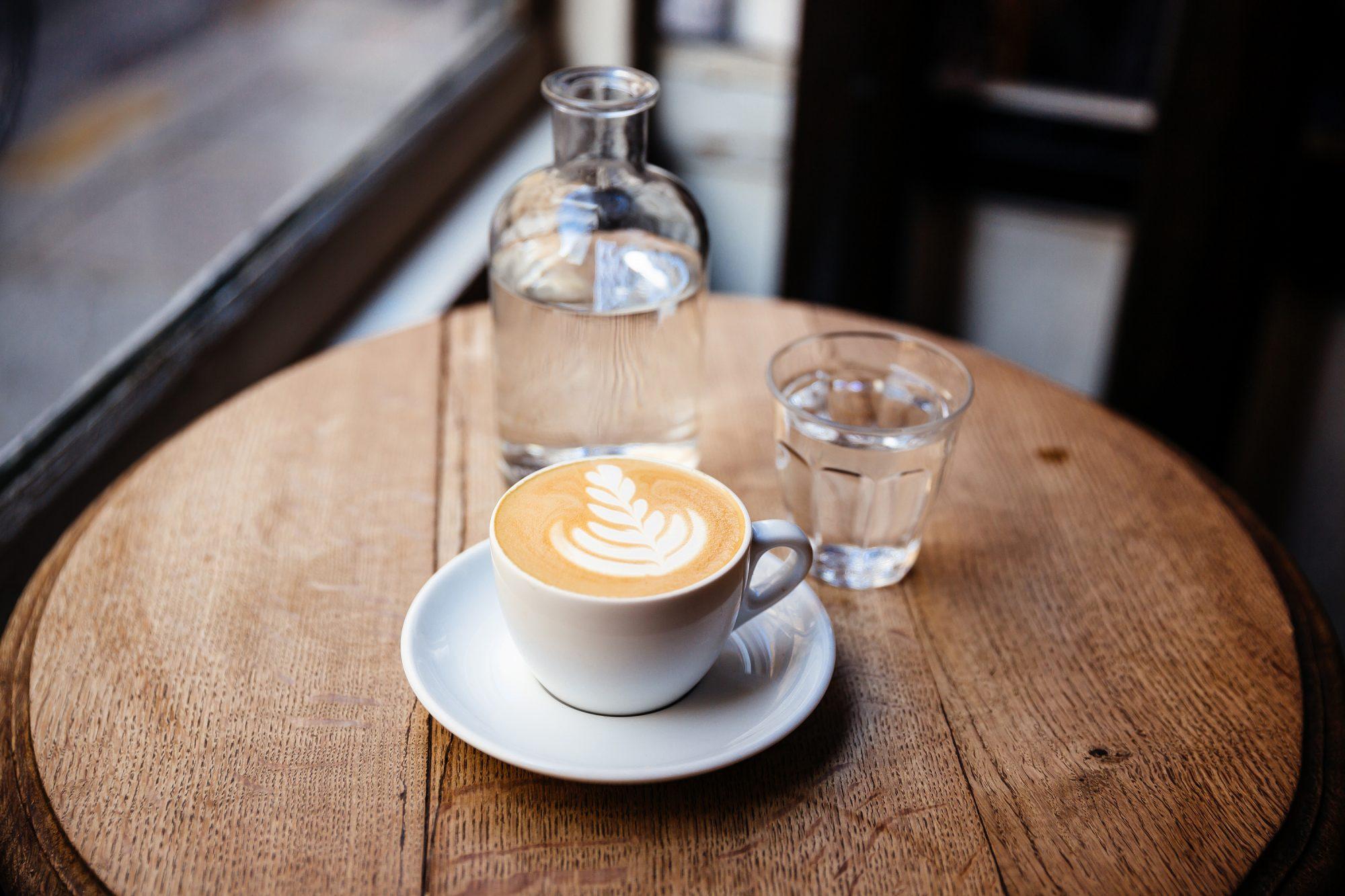 TAZA DE CAPUCHINO Y AGUA SIN GAS SOBRE LA MESA EN UNA CAFETERÍA, VISTA LATERAL