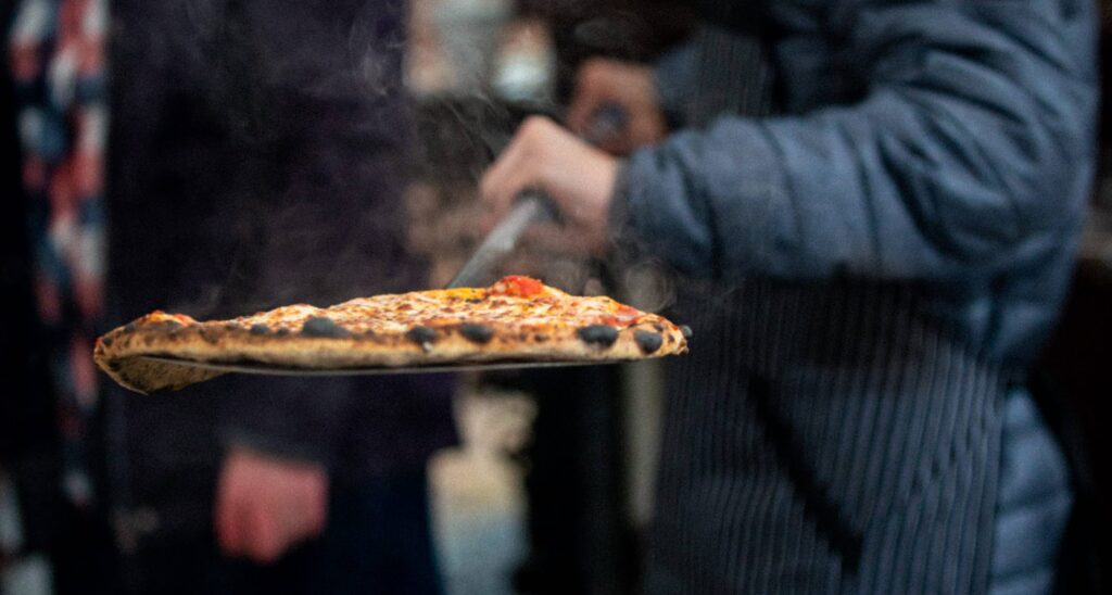 PIZZA ON PERFORATED PIZZA PEEL SCALED CÓMO HACER LA PIZZA LEOPARDO PERFECTA (PIZZA CARBONIZADA)